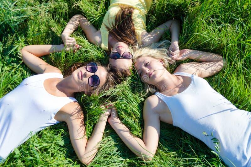 Drie gelukkige tienermeisjes die op groen gras liggen en handen houden royalty-vrije stock foto's