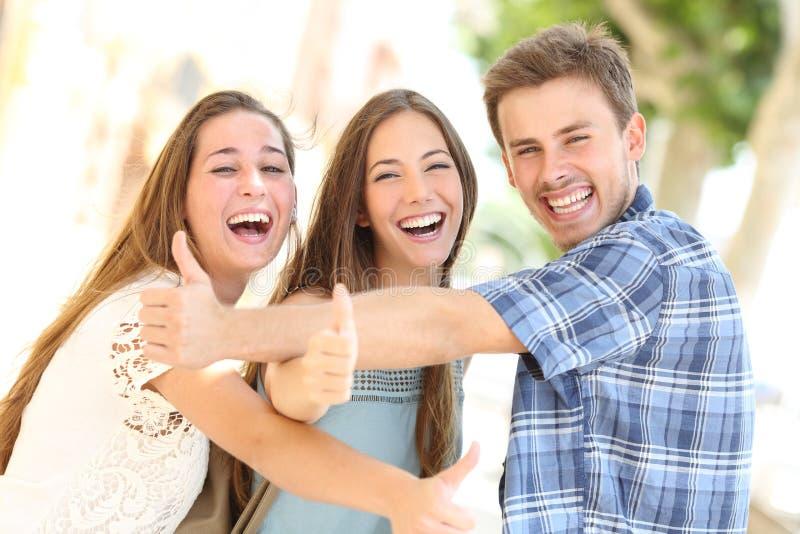 Drie gelukkige tieners die met omhoog duimen lachen stock foto's