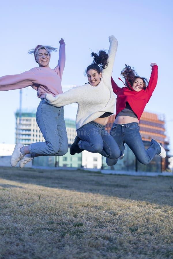 Drie gelukkige vrienden die van tienermeisjes hoog in blauwe hemel op de zomer in openlucht achtergrond springen royalty-vrije stock afbeelding