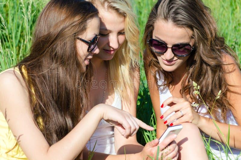 Drie gelukkige vrienden van het tienermeisje en mobiele telefoon stock foto