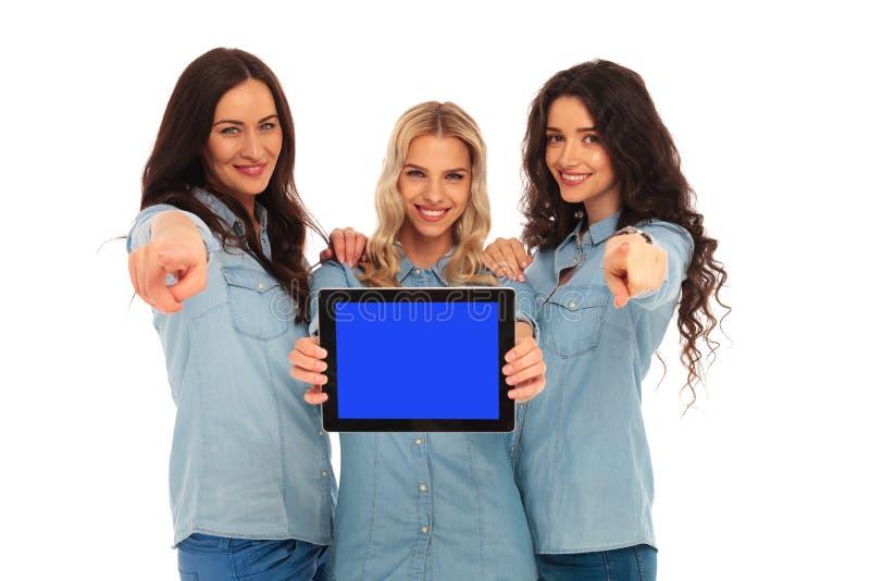 Drie gelukkige vrouwen die het scherm van de tablet voorstellen en F richten royalty-vrije stock afbeeldingen