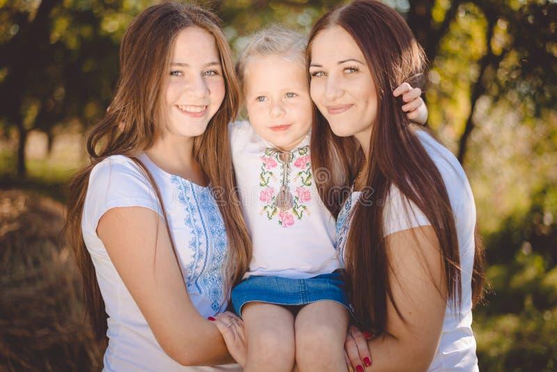 Drie gelukkige zusters die en vreugdevol in de zomerpark koesteren glimlachen royalty-vrije stock afbeelding
