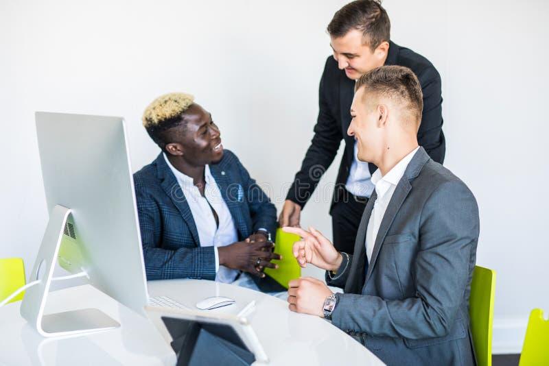 Drie gemengde raszakenman, één rijpt en twee jonge degenen zittend bij lijst tijdens vergadering stock afbeelding