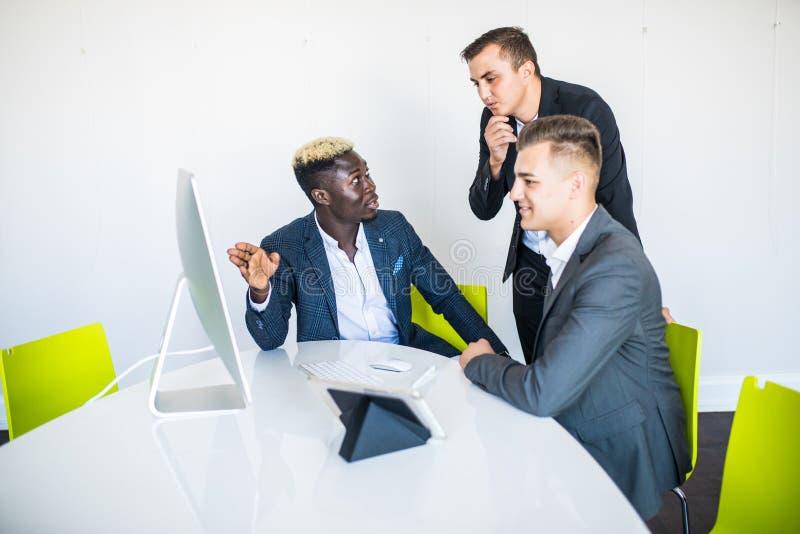 Drie gemengde raszakenman, één rijpt en twee jonge degenen zittend bij lijst tijdens vergadering stock foto's