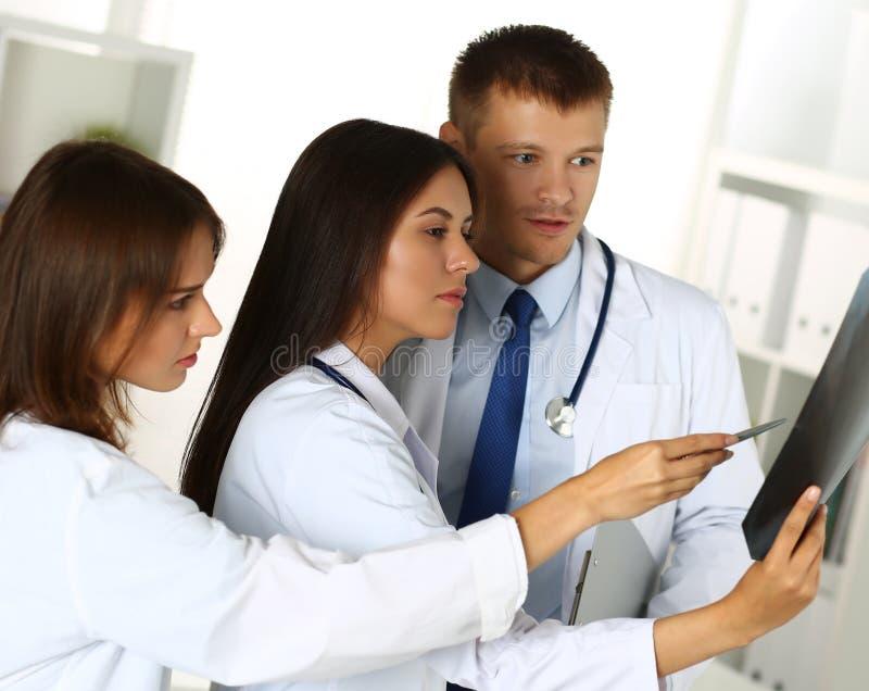 Drie geneeskunde artsen die x-ray fotografie onderzoeken stock foto