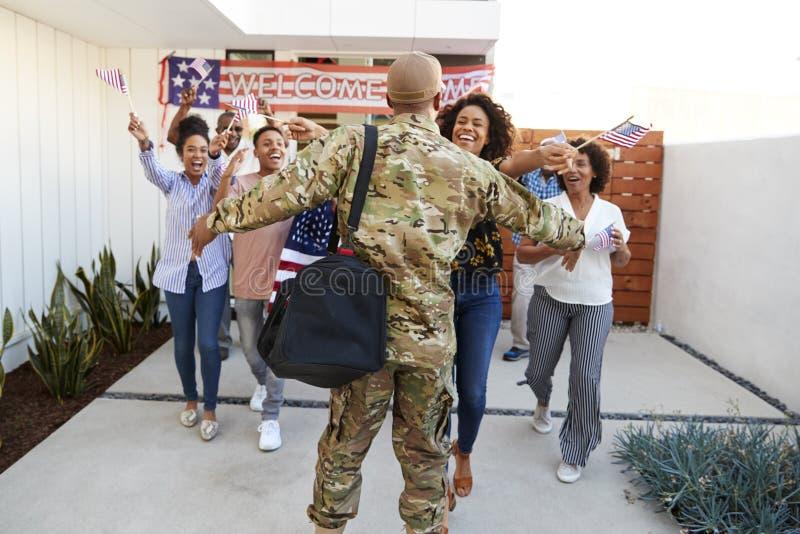 Drie generatie Afrikaanse Amerikaanse familie die achter millennial militair welkom heten die huis, achtermening terugkeren royalty-vrije stock afbeeldingen