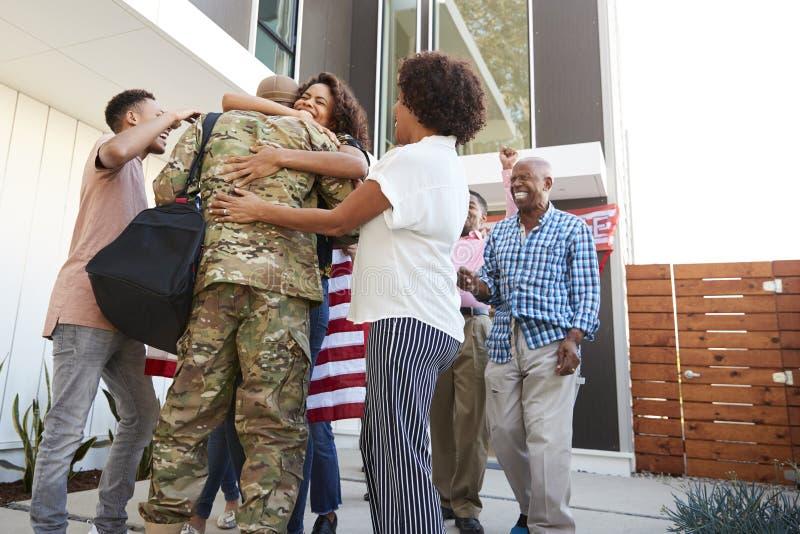Drie generatie Afrikaanse Amerikaanse familie die millennial mannelijke militair welkom heten die huis, lage hoekmening terugkere royalty-vrije stock foto
