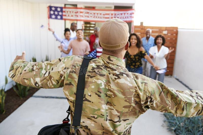 Drie generatie Afrikaanse Amerikaanse familie die millennial militair welkom heten die huis, achtermening, nadruk op voorgrond te stock foto