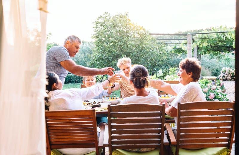 Drie generaties één familie hebben diner in de zomertuin stock afbeelding
