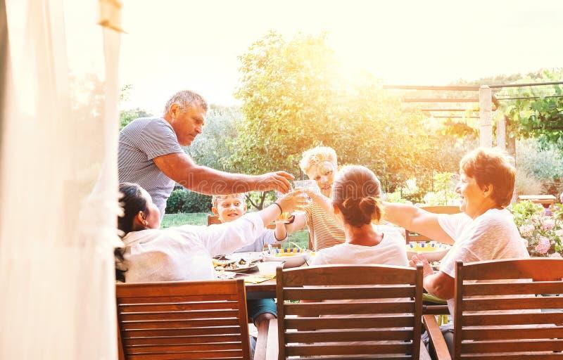 Drie generaties ??n familie hebben diner in de zomertuin royalty-vrije stock foto