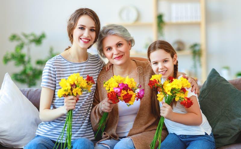 Drie generaties van gelukkige familiegrootmoeder, moeder en dochter met bloemen thuis royalty-vrije stock foto's