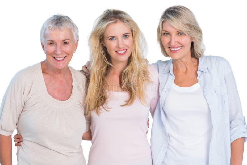Drie generaties van gelukkige vrouwen die bij camera glimlachen stock foto's
