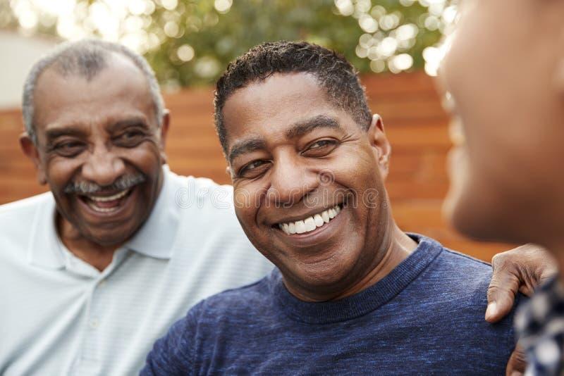 Drie generaties van huiselijke mannen die, sluiten omhoog samen lachen royalty-vrije stock afbeelding