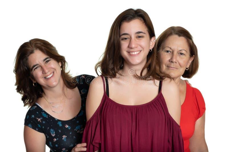 Drie generaties van Latijnse vrouwen die en - op een witte achtergrond glimlachen koesteren royalty-vrije stock fotografie