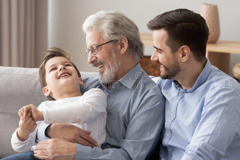 Drie generaties van mensen hebben pret die samen ontspannen stock afbeelding