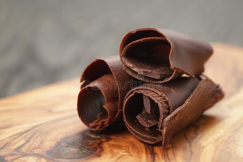 Drie gepelde chocoladekrullen op olijf houten raad royalty-vrije stock afbeeldingen