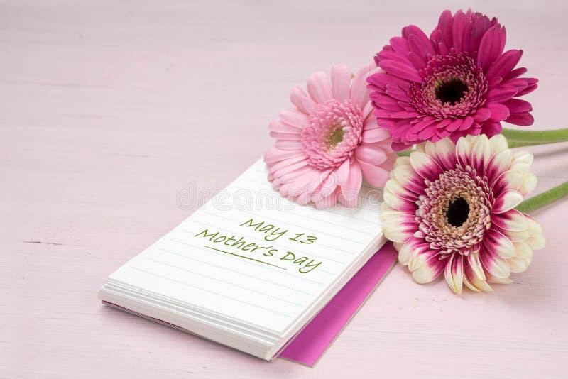 Drie gerberabloemen die op een blocnote, pastelkleur roze colore liggen royalty-vrije stock foto's