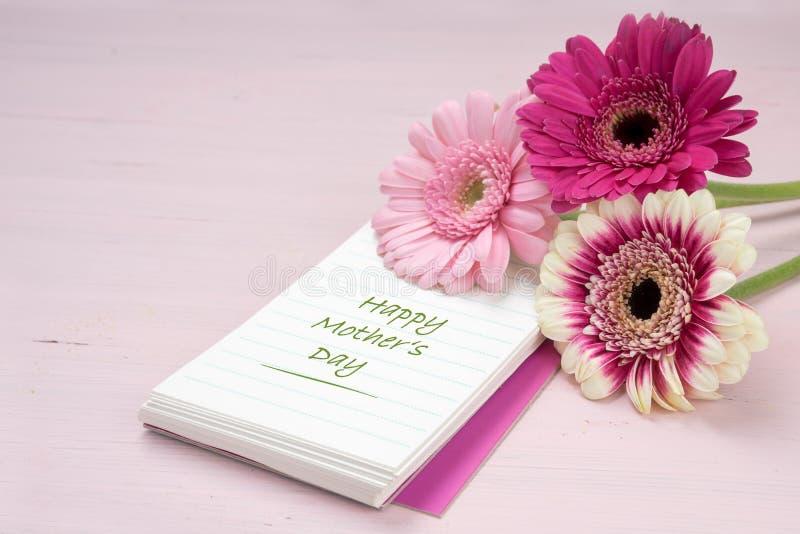 Drie gerberabloemen die op een blocnote, pastelkleurroze liggen kleurden achtergrond met exemplaarruimte, tekst Gelukkige Moederd stock foto