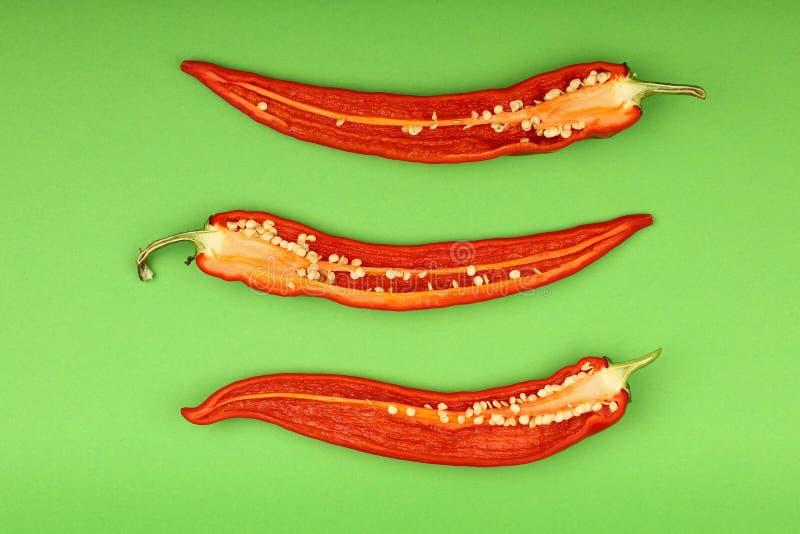 Drie gesneden roodgloeiende Spaanse peperpeper op Groenboek stock afbeelding