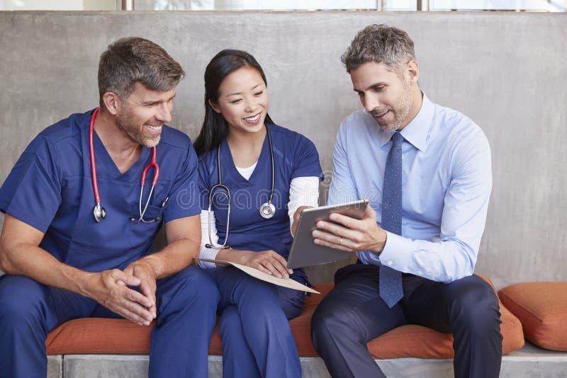 Drie gezondheidszorgarbeiders zitten samen gebruikend tabletcomputer royalty-vrije stock afbeelding
