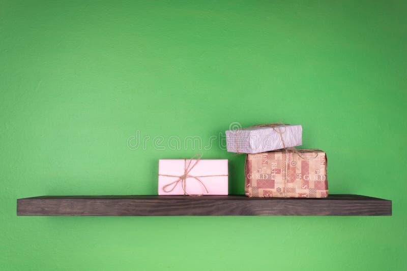 Drie giftdozen verschillende kleuren schikten in een groep op een zwarte die plank op de groene muur wordt geplaatst stock fotografie