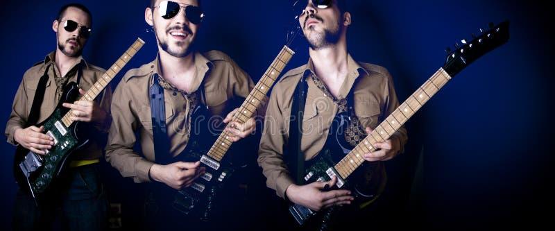 Drie gitaarspelers stock foto's