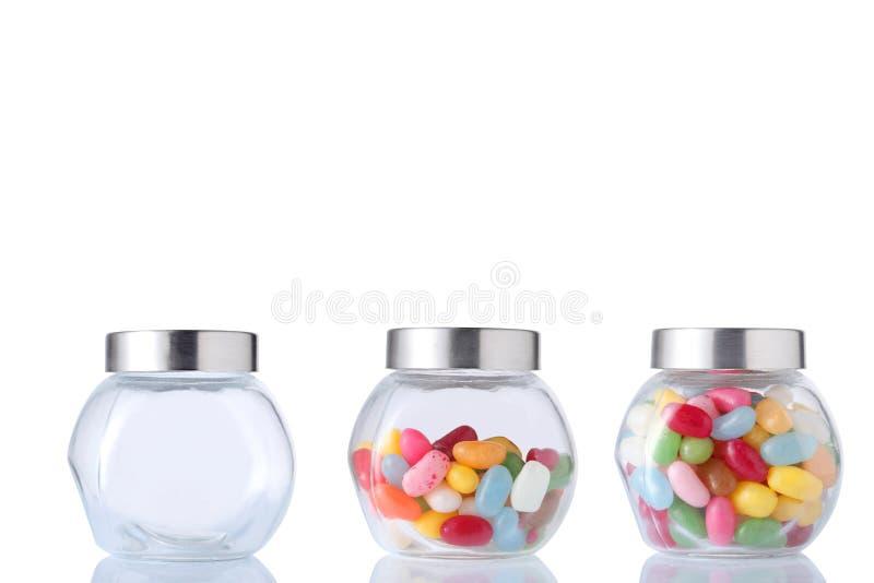 Drie glaskruik, één lege, halve leeg en één hoogtepunt van gekleurd suikergoed geïsoleerd op witte achtergrond met het knippen va stock foto