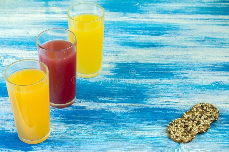 Drie glazen frisdranken zijn op een blauwe achtergrond Een paar koekjes die rond liggen De zomerdranken en gezonde levensstijl stock fotografie