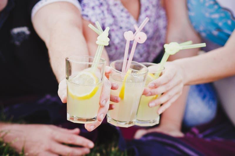 Drie glazen limonade in de handen van mensen royalty-vrije stock afbeelding