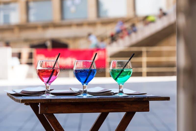 Drie glazen met kleurrijke cocktails dichtbij de koffie, Siurana, Catalunya, Spanje Exemplaarruimte voor tekst stock afbeeldingen