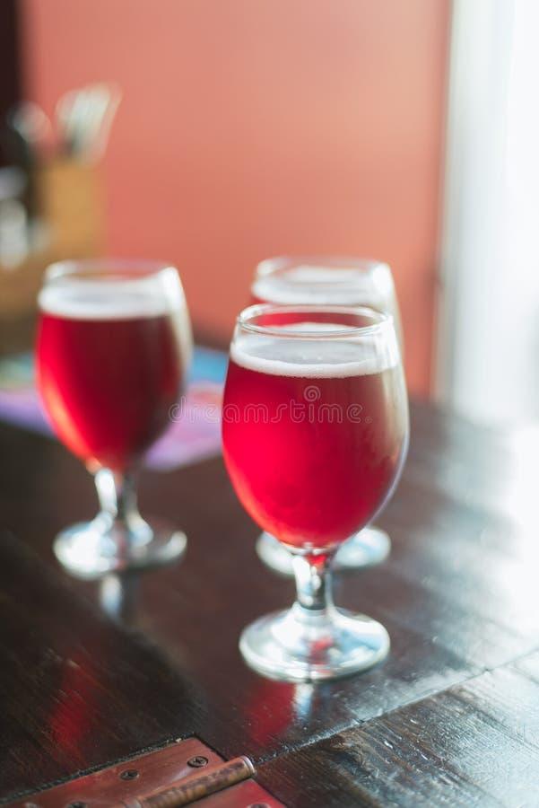 Drie glazen met rode wijn op een houten lijst De glazen kersenbier zijn op de lijst Er zijn niemand in het kader royalty-vrije stock fotografie