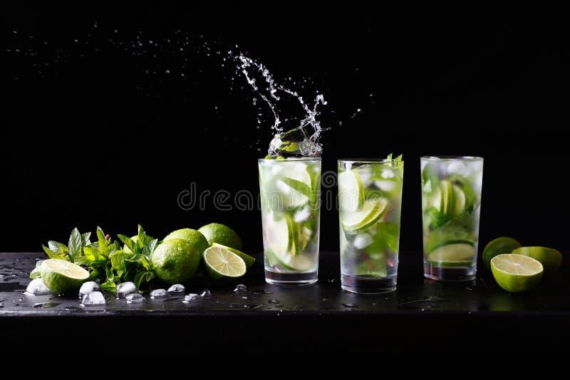 Drie glazen van het verfrissen van Mojito-de cocktail van de rumalcohol op de bar, plonsen in een glas Partijcocktail Kalk, ijs e royalty-vrije stock foto