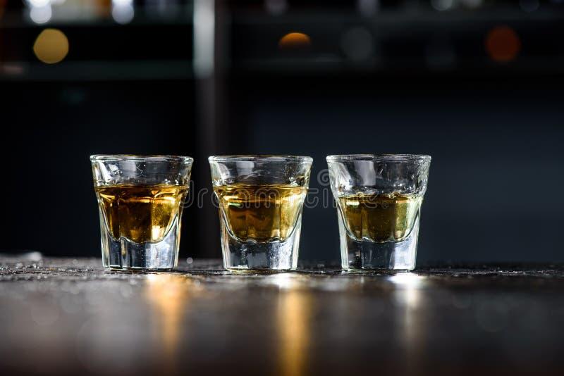 Drie glazen whisky op een donkere houten bar in een nachtclub royalty-vrije stock afbeeldingen