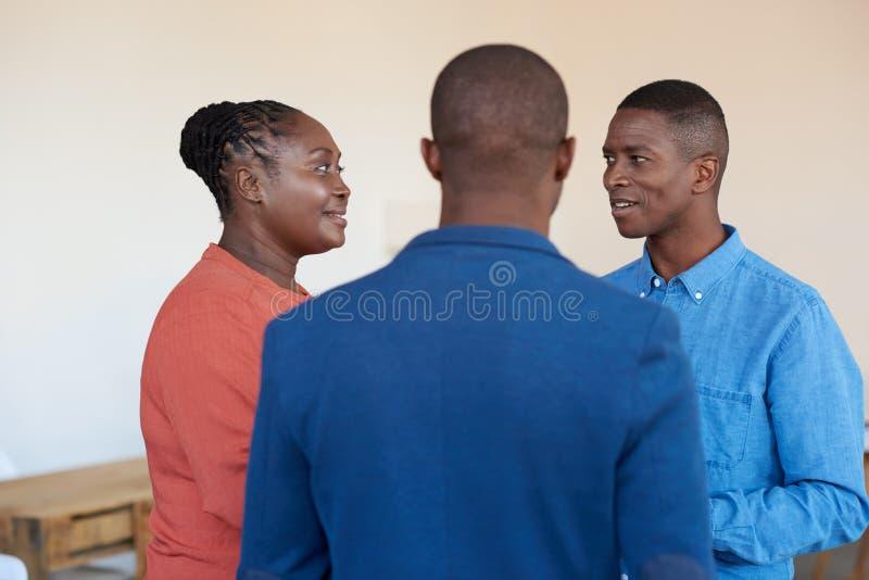 Drie glimlachende Afrikaanse bureaucollega's die samen op het werk spreken stock afbeelding
