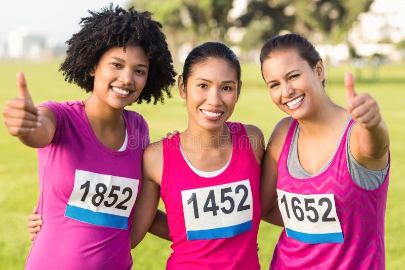 Drie glimlachende agenten ondersteunend de marathon van borstkanker stock afbeeldingen
