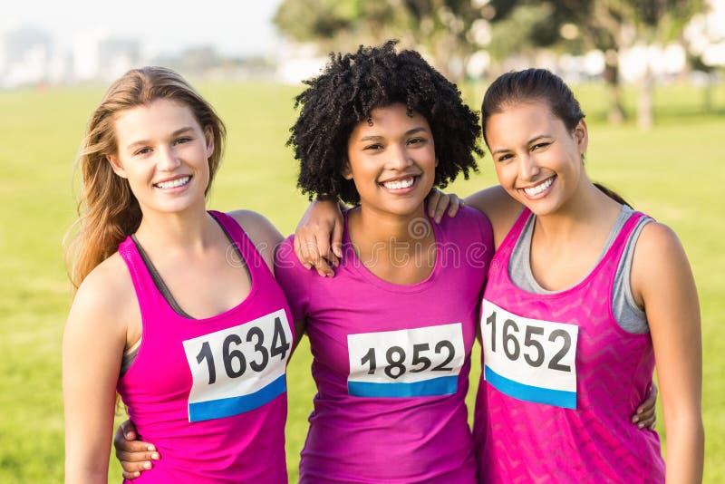 Drie glimlachende agenten ondersteunend de marathon van borstkanker royalty-vrije stock foto