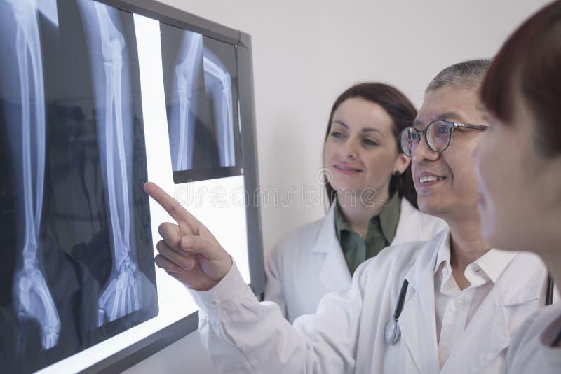 Drie glimlachende artsen die röntgenstralen van menselijke beenderen bekijken, één arts richt stock foto's