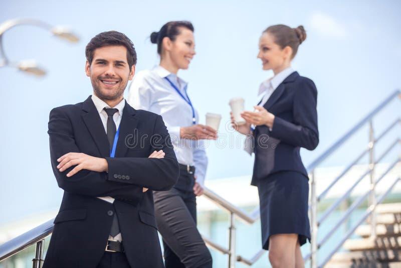 Drie glimlachende bedrijfsmensen die zich op treden bevinden stock foto's