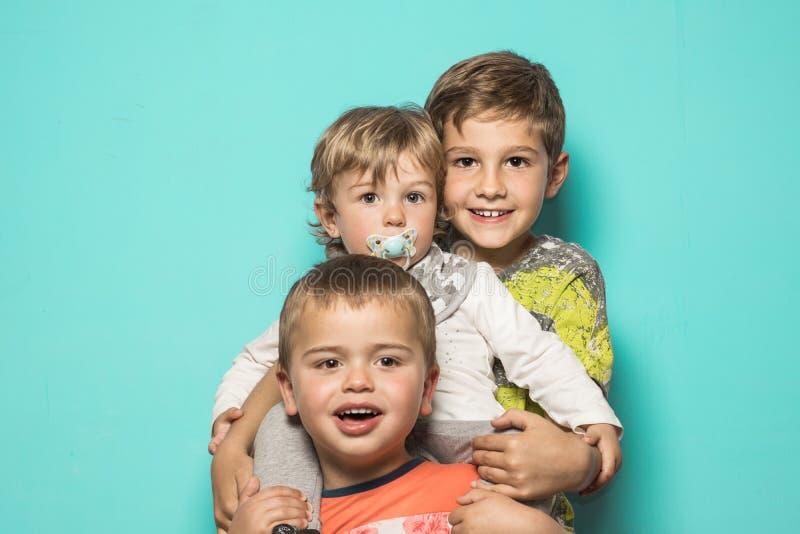 Drie glimlachende kinderen die elkaar koesteren stock fotografie