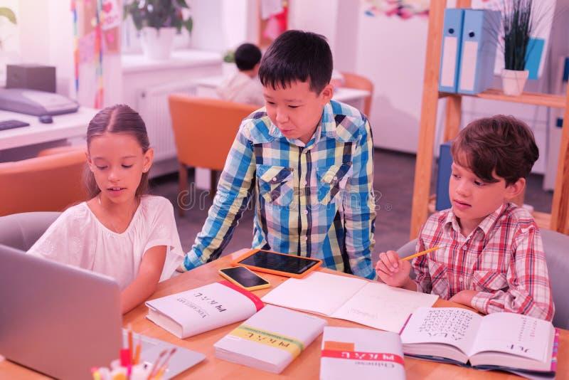 Drie glimlachende kinderen die elkaar met thuiswerk helpen royalty-vrije stock foto