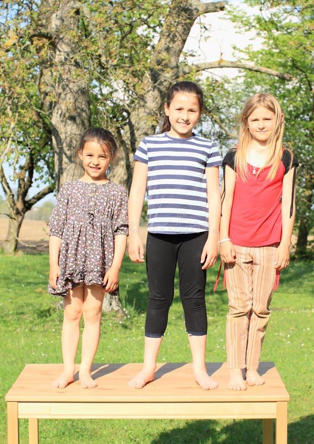 Drie glimlachende meisjes die zich op de lijst bevinden stock afbeeldingen