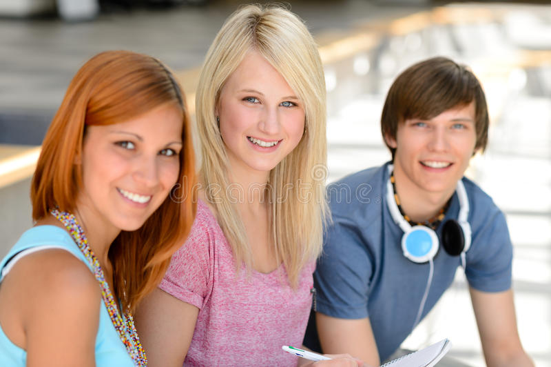 Drie glimlachende studentenvrienden die camera bekijken stock fotografie
