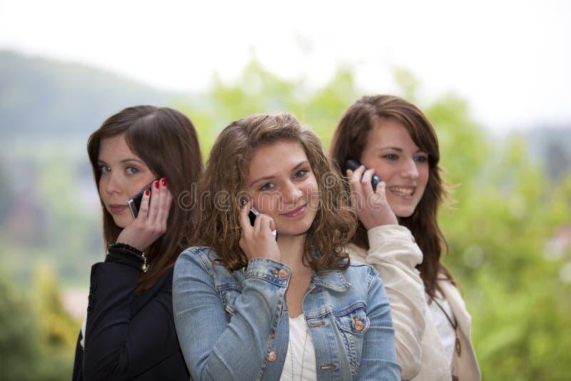 Drie glimlachende tieners met cellphones royalty-vrije stock fotografie