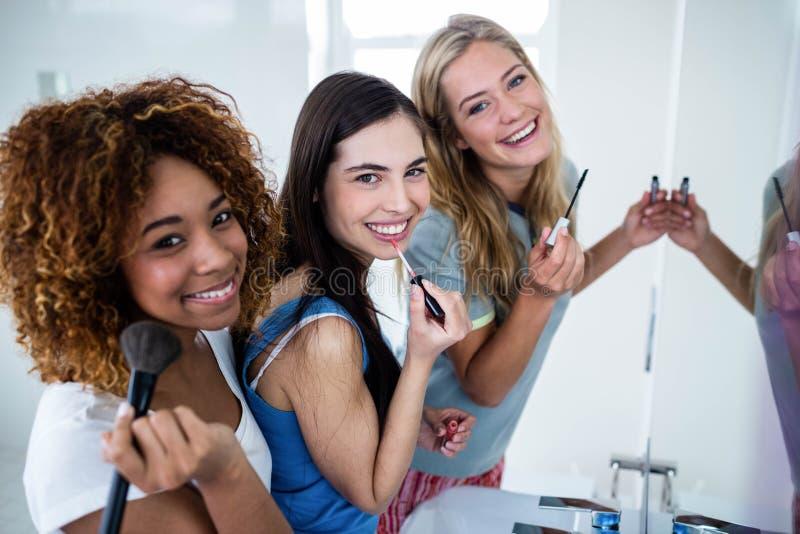 Drie glimlachende vrienden die make-up samenbrengen op royalty-vrije stock fotografie