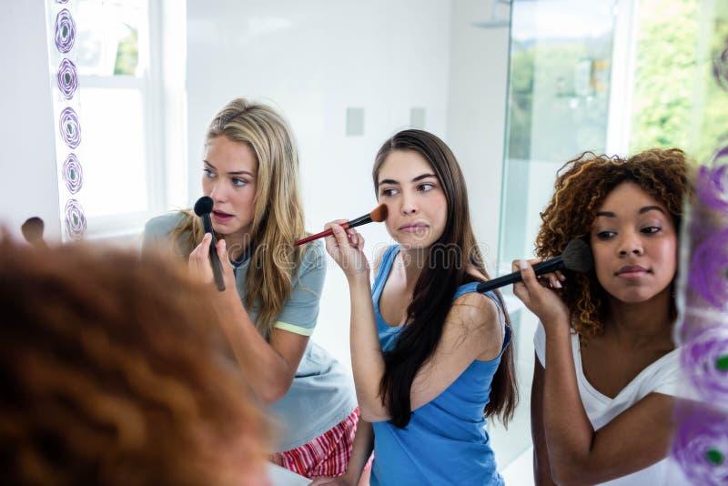 Drie glimlachende vrienden die make-up samenbrengen op royalty-vrije stock foto's