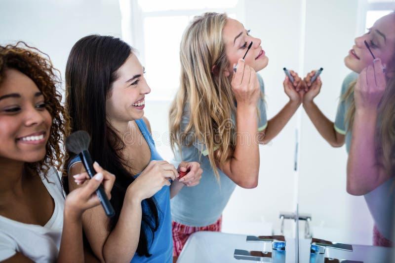 Drie glimlachende vrienden die make-up samenbrengen op stock afbeeldingen