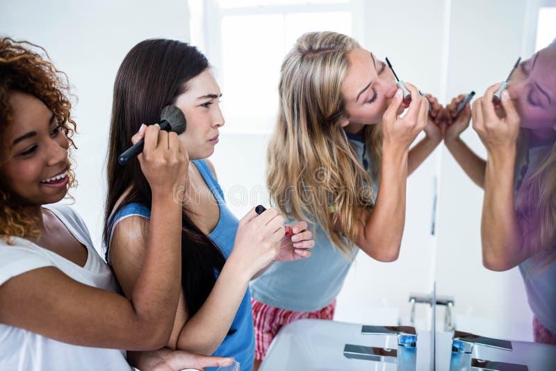 Drie glimlachende vrienden die make-up samenbrengen op stock afbeelding