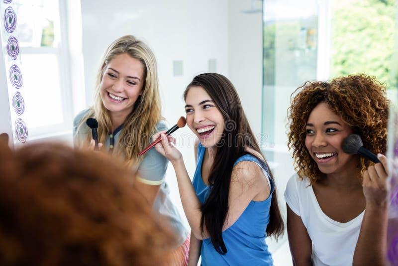 Drie glimlachende vrienden die make-up samenbrengen op stock foto's