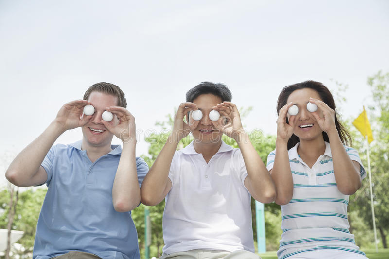 Drie glimlachende vrienden die op een rij golfballen voor hun ogen steunen royalty-vrije stock foto