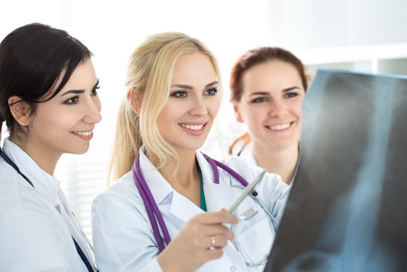 Drie glimlachende vrouwelijke artsen die x-ray beeld bekijken stock foto